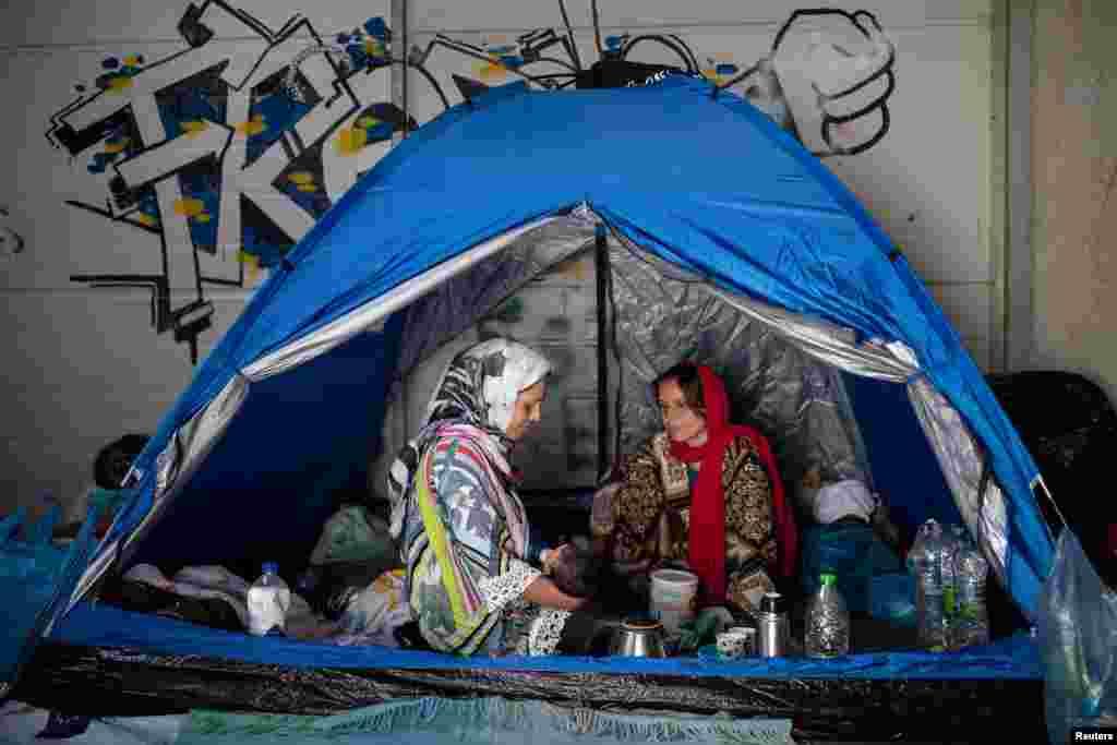 Një grua e ushqen me qumësht foshnjën e saj të porsalindur derisa kanë gjetur strehë në një depo pranë një kampi të ri të përkohshëm.