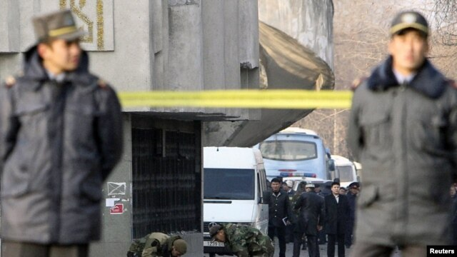 Kyrgyz policemen stand guard as security personnel work on the site of a blast in Bishkek on November 30, 2010. Authorities blamed it on a previously unknown group.