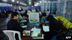 Afghan election workers sort ballot papers during an audit of the presidential runoff vote in the country's general election at a counting center in Kabul on August 25.