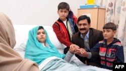 Malala Yousafzai, who was shot in the head by Taliban gunmen for campaigning for the right to an education, sitting on her bed amid her mother Toorpekai Yousufzai (L), brothers Khushal Khan (3rd R) and Apal Khan (R) and father