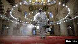 Një punëtor duke dezinfektuar një xhami në Stamboll.