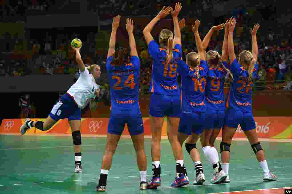 Russia's Anna Sen (left) makes a free throw against Dutch defenders during a preliminary match in women's handball.