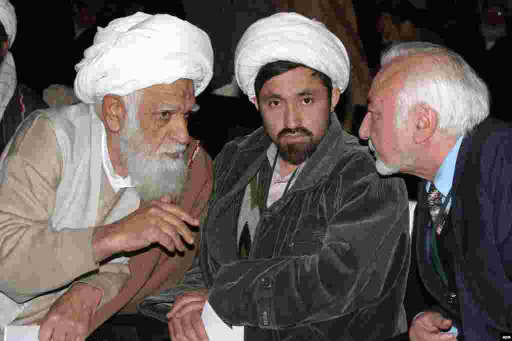 Delegates discuss issues at the Loya Jirga in Kabul in December 2003 (epa) - Efforts to balance the numerous demands reflect the government's limited power. Major cities are under its control, but beyond the capital, its authority is shaky. In the south, an insurgency is directly aimed against the central authorities; in the north, loyalty to local warlords makes it difficult for the government to impose its will.
