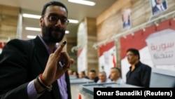 Sirijac pokazuje mastilo na prstu tokom glasanja na predsedničkim izborima u Damasku, 26. maj 2021.