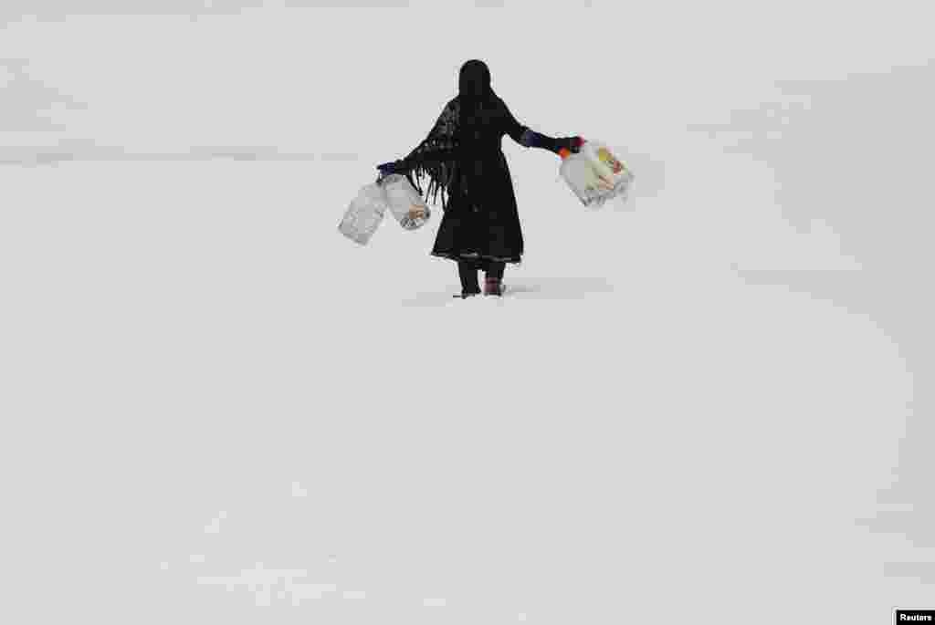 An Afghan girl carries empty water containers during a snowfall in Kabul on February 6. (Reuters/Mohammad Ismail)