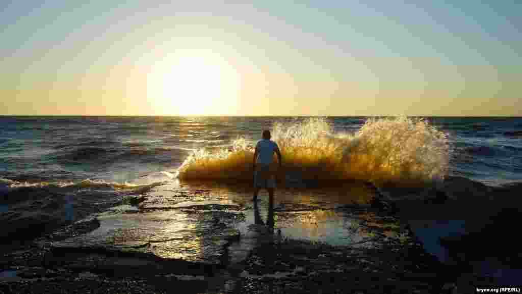 Хлопчик на буні перед хвилями