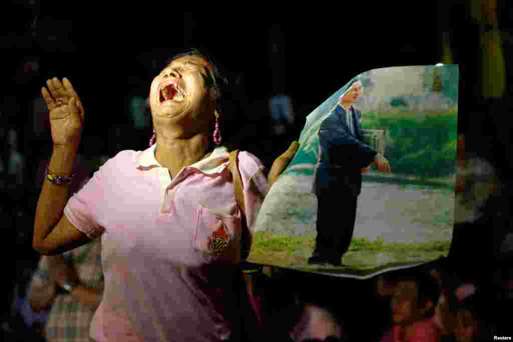 A woman in Bangkok cries as she holds up a portrait of Thailand's King Bhumibol Adulyadej, who died on October 13. (Reuters/Chaiwat Subprasom)
