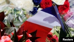 A bouquet of flowers and a French flag are seen as people pay tribute near the scene of the attack in Nice.