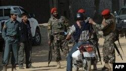 Ауғанстан қауіпсіздік қызметкерлері мотоцикль мінген адамды тексеріп жатыр. Көрнекі сурет.
