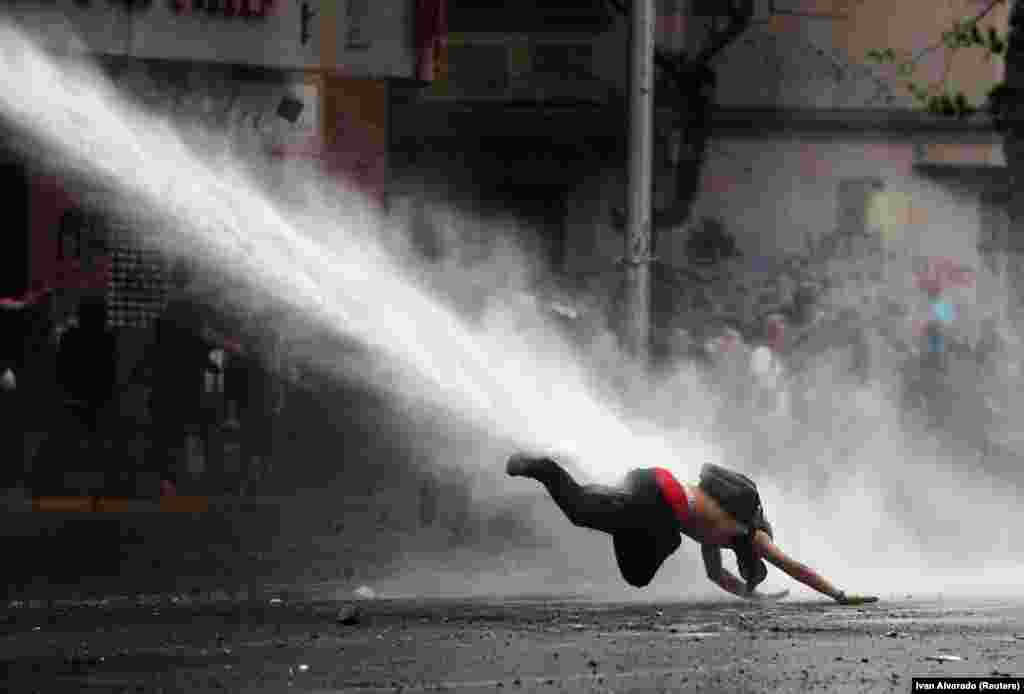 A demonstrator dives to the ground after being hit by spray from a water cannon during an anti-government protest in Santiago, Chile. (Reuters/Ivan Alvarado)