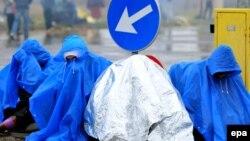 Мигранты в дождевиках на хорватско-словенской границе
