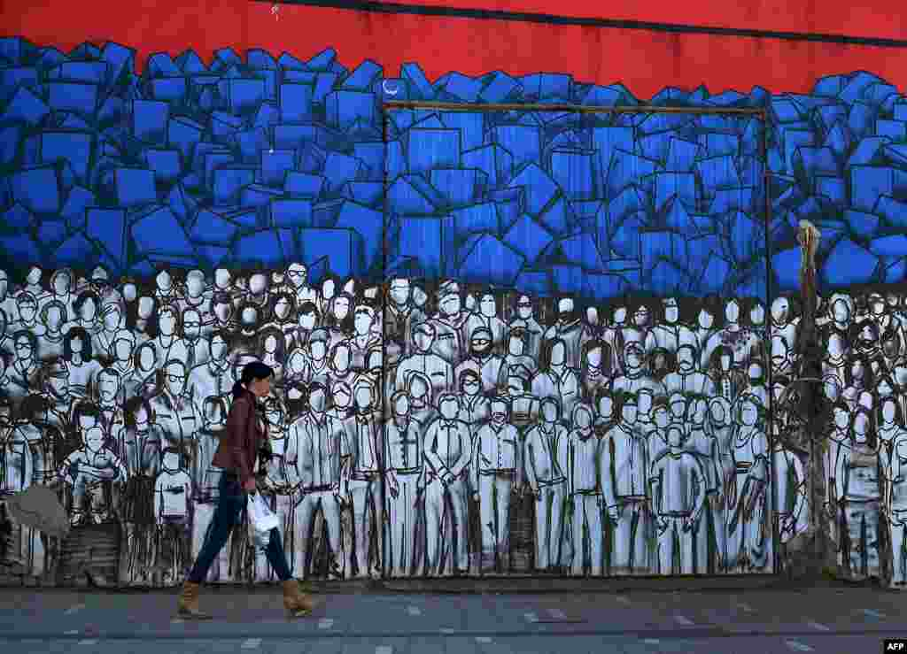 A woman walks past a mural depicting many famous Serbs and the Serbian national flag in Belgrade. (AFP/Andrej Isakovic)