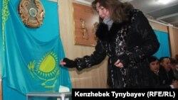 Избиратель опускает бюллетень в урну на внеочередных парламентских выборах. Алматы, 15 января 2012 года.