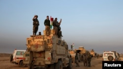 Iraqi Kurdish Peshmerga forces stand on a military vehicle in the town of Bashiqa, east of Mosul, during an operation to attack Islamic State militants in Mosul, on November 7.