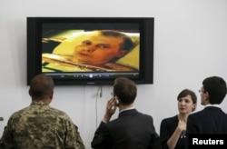 Учасники пресс-конференции смотрят видео с одним из пленных военнослужащих. Киев, 18 мая 2015 года