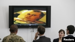 Ukrainian journalists and a serviceman look at a video of Russian soldiers allegedly captured by Ukrainian troops before a news conference in Kyiv on May 18.