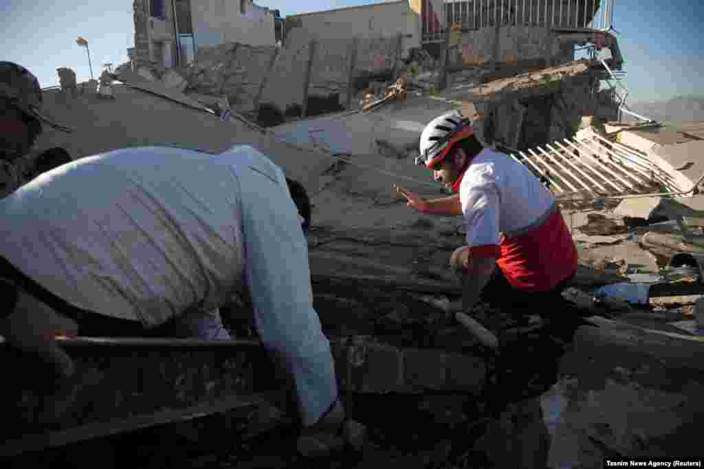 Rescue workers search for victims under the rubble of a collapsed building in Sarpol-e Zahab.