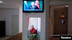 Мужчина в инвалидной коляске смотрит телевизор, где показывают выступление президента России Владимира Путина.