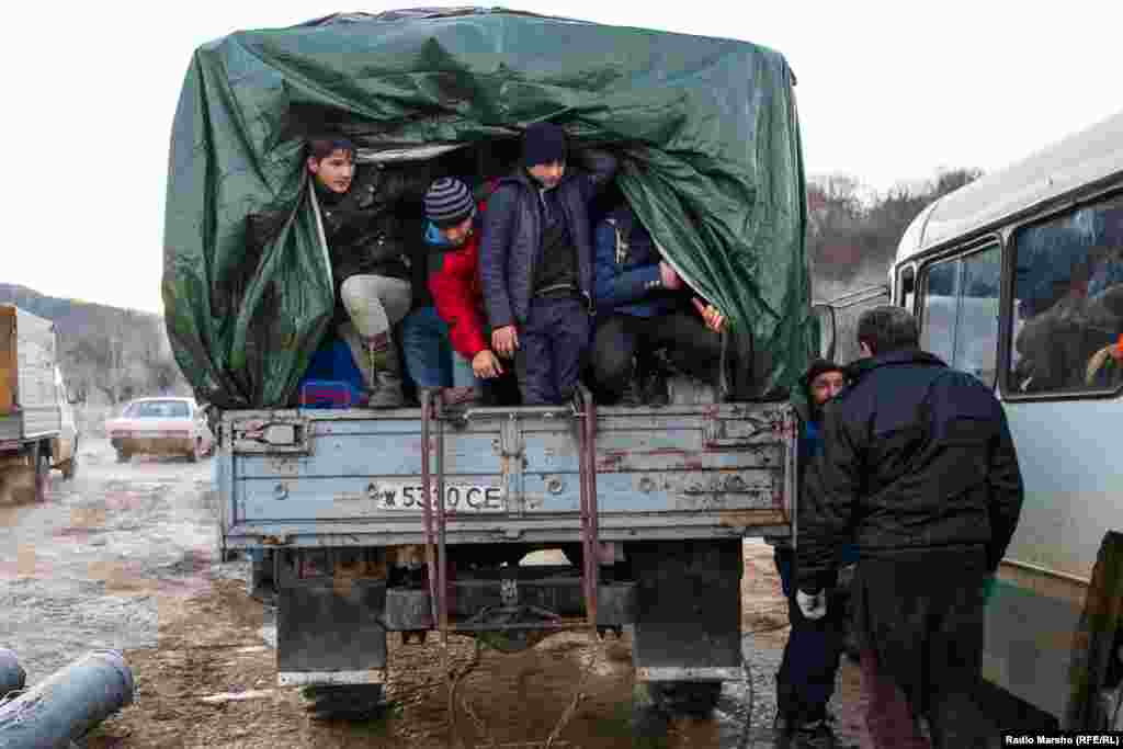 Pickers, many of them young boys, scramble into the back of a pickup truck for the journey across muddy, rutted pathways.