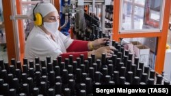 Сотрудница в медицинской маске на работе в цехе розлива вина на винзаводе «Массандра», архивное фото