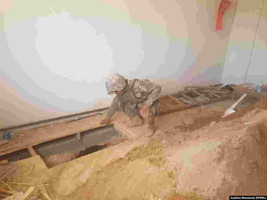 Үйдің төбесін тесіп, еден астына өтіп қадалған снарядты саперлардың қалай қазып алғанын Азаттық тілшісі көрді. Әуелі снарядтың айналасын екі метрге жуық терең етіп қазған саперлар оны еппен суырып алды. Арыс, Түркістан облысы, 29 маусым 2019 жыл.