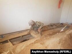 Еден астына өтіп кеткен снаряд айналасын қазып жүрген сапер. Түркістан облысы, Арыс қаласы 29 маусым 2019 жыл.