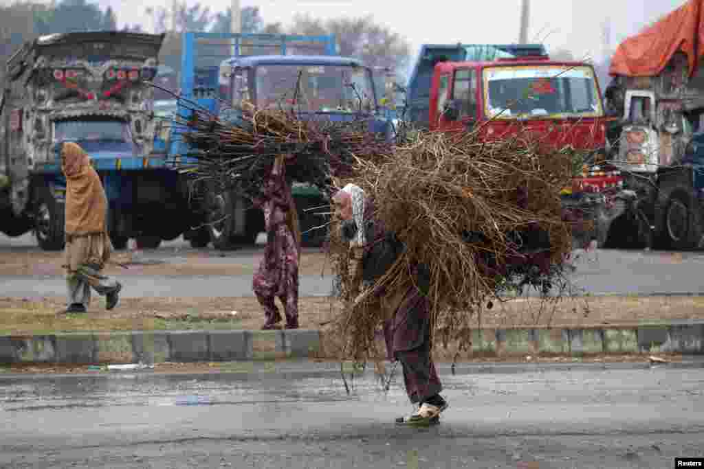 A Pakistani man and a woman carry tree branches, used as fuel for cooking, on the outskirts of Islamabad, on December 11. (Reuters/Mian Khursheed)