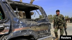 An Afghan National Army soldier inspects the wreckage of vehicles at the site of a suicide attack that targeted a NATO convoy in Jalalabad on April 10.