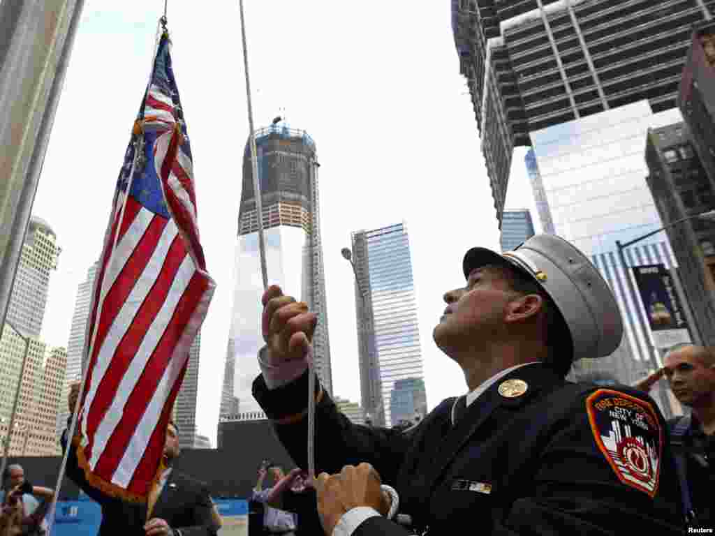 New York Fire Department Battalion Commander Tom Currao raises a flag outside the World Trade Center construction site at the 9/11 Memorial Visitors Center in New York on September 9. (Photo by Brian Snyder for Reuters)