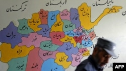 A policeman walks past a map of Afghanistan.