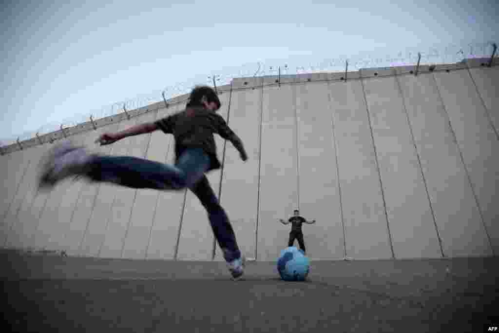 Palestinian children play football in front of the controversial Israeli separation barrier in the West Bank village of Abu Dis on the outskirts of Jerusalem. (AFP/Ahmad Gharabli)