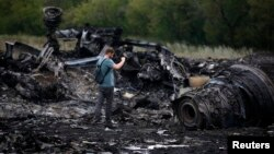 A journalist takes photographs at the site of the Malaysia Airlines Boeing 777 plane crash near the settlement of Hrabovo, in the Donetsk region, on July 18, one day after the crash, which killed all 298 people aboard.