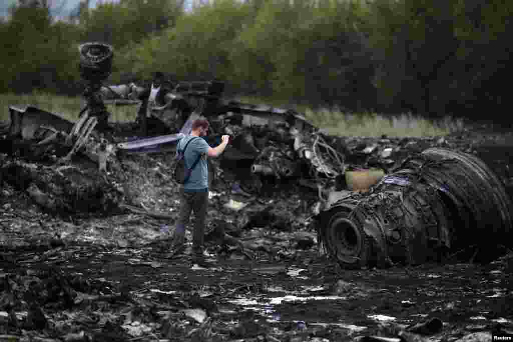 A journalist takes photographs at a crash site on July 18.