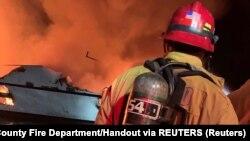 Сотрудник противопожарной службы стоит возде горящего судна Conception. США, остров Санта-Круз. 2 сентября 2019 года.