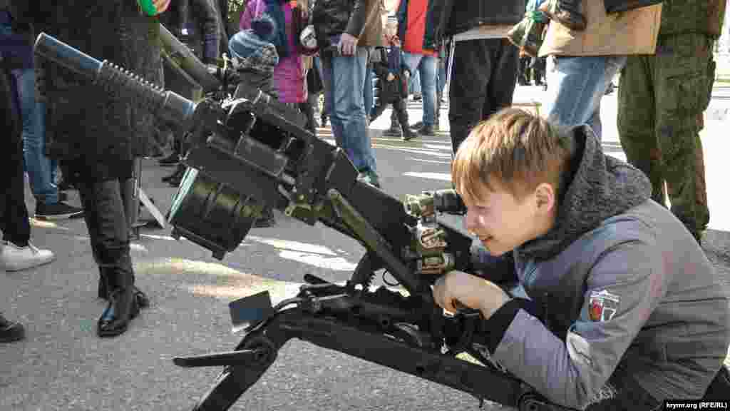 A child looks through the sights of a grenade launcher at an exhibition of Syrian weapons in Sevastopol on April 3.