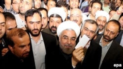 Presidential candidate Hassan Rohani (center) shows his ballot to the media as he casts his vote at the Imam-Reza mosque in southern Tehran.