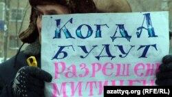 """Участник акции протеста держит плакат с надписью: """"Когда будут разрешены митинги?"""" Уральск, 24 марта 2012 года."""