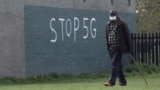 Чоловік у масці на обличчі під час спалаху коронавірусної хвороби (COVID-19) проходить повз графіті з написом «STOP 5G» в Лондоні, Великобританія, 8 квітня 2020 року.