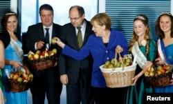 """""""Jedna jabuka na dan, Putin iz kuće van"""", poručio je jedući s kancelarkom Angelom Merkel i ministrima iz pune košarice i pozivajući sve da jedu """"po pet jabuka dnevno"""" i tako podrže njemačke poljoprivrednike (Berlin, 2015. godine)"""