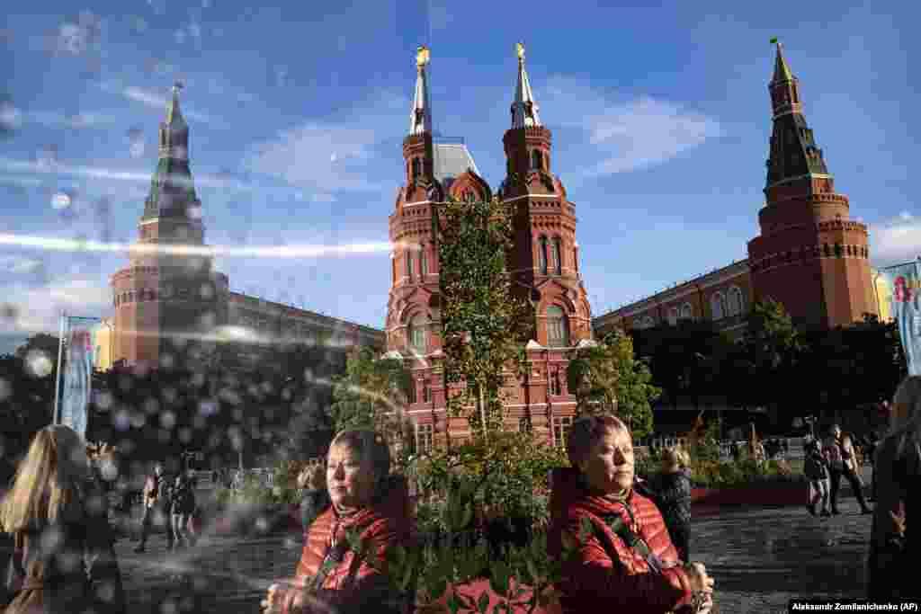 Люди отражаются в зеркале на Манежной площади в Москве