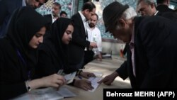 An elderly man registers to cast his ballot at a polling station in Tehran on May 19, 2017.
