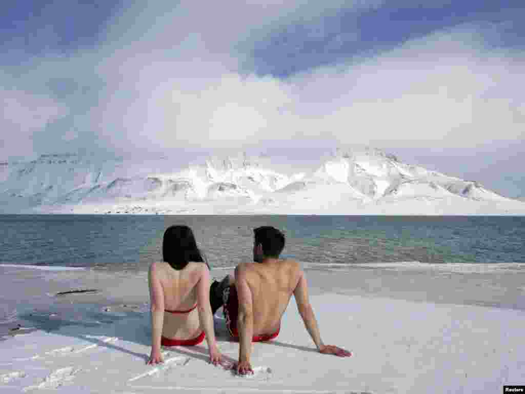 "Climate activists Lesley Butler and Rob Bell (R) ""sunbathe"" on the edge of a frozen fjord in the Norwegian Arctic town of Longyearbyen April 25, 2007. The activists are warning that global warming could thaw the Arctic and make the sea warm enough for people to swim and sunbathe in. REUTERS/Francois Lenoir"