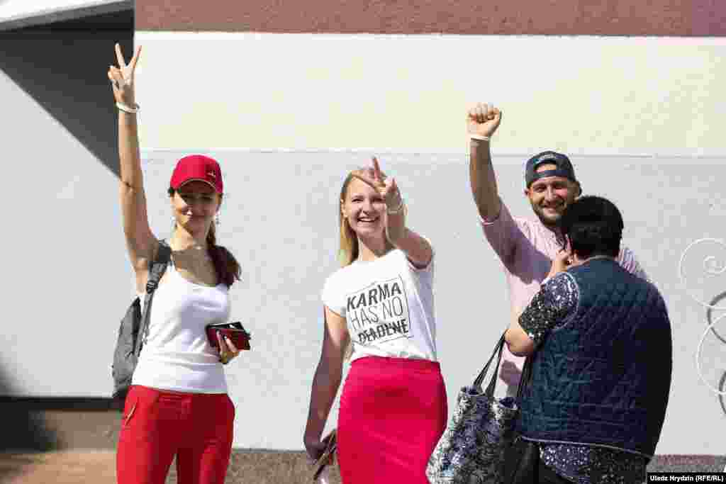 Voters show signs used by the opposition at School 41 in Minsk.