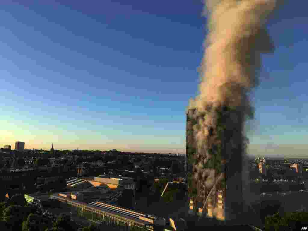 """Smoke pours from a 27-story apartment building in west London on the morning of June 14. The fire brigade said 40 fire engines and 200 firefighters had been called to the blaze in Grenfell Tower, which has 120 flats. Officials say there have been a """"number of fatalities."""" (AFP/Natalie Oxford)"""