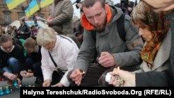 Люди зажигают свечи в День памяти жертв Голодомора в Украине. Львов, 23 ноября 2013 года.