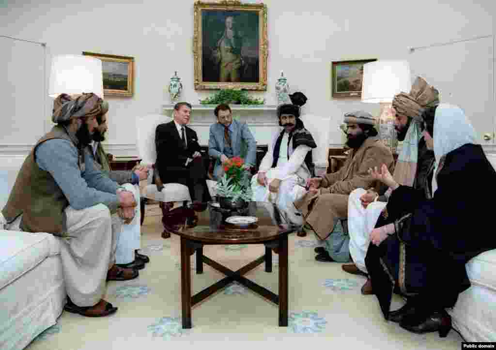 """U.S. President Ronald Reagan meeting with Afghan mujahedin leaders in 1983. Soon the United States, together with Saudi Arabia, was funneling hundreds of millions of dollars each year to anti-Soviet militants in Afghanistan in an effort to """"bleed""""the Soviet Union. (U.S. Government photo)"""