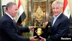 Iraqi Defense Minister Khaled al-Obeidi (left) meets with outgoing U.S. Defense Secretary Chuck Hagel in Baghdad on December 9.