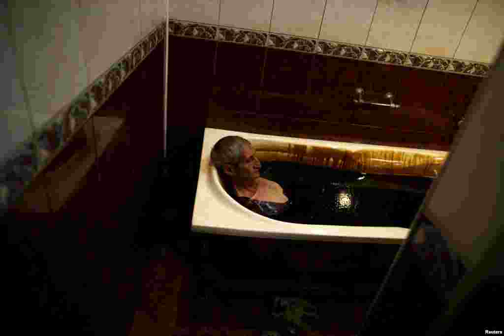 A man lies in a bathtub filled with crude oil during a health therapy session at the Naftalan Health Center in Baku, Azerbaijan. According to Hashim Hashimov, a medical specialist at the center, the oil can heal more than 70 diseases, including neurological diseases, skin conditions, and impotence. Centers like Naftalan attract people coming from Russia, Kazakhstan, and Germany, Hashimov told Reuters. (Reuters/Stoyan Nenov)