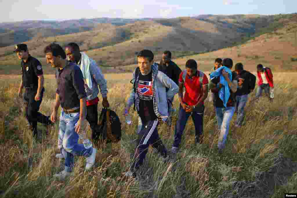 Migrants are escorted by a Serbian border officer near the southern town of Presevo after being caught illegally entering the country from Macedonia.