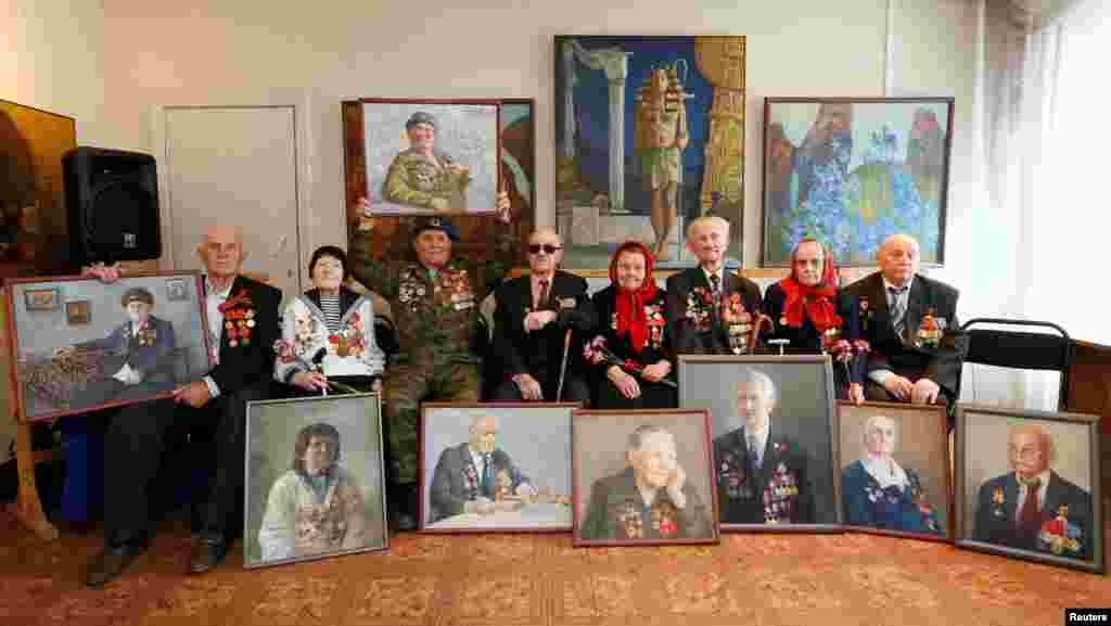 RussiaN World War II veterans pose for a picture with oil portraits of themselves created by students of Krasnoyarsk Art College as presents for the upcoming Victory Day Krasnoyarsk, Siberia, on April 28. (Reuters/Ilya Naymushin)